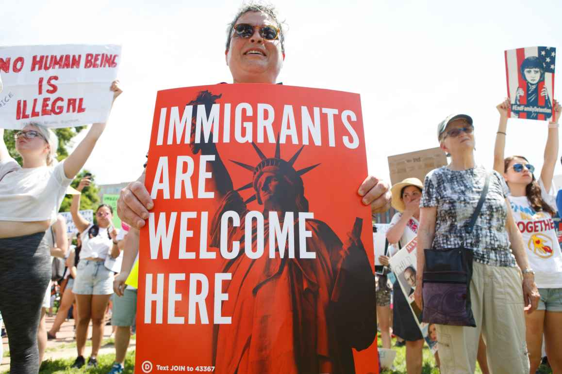 person holding 'immigrants are welcome here' sign at rally