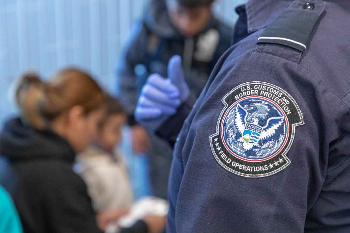 Badge on Customs and Border Patrol officer's uniform in focus with family being inspected in background