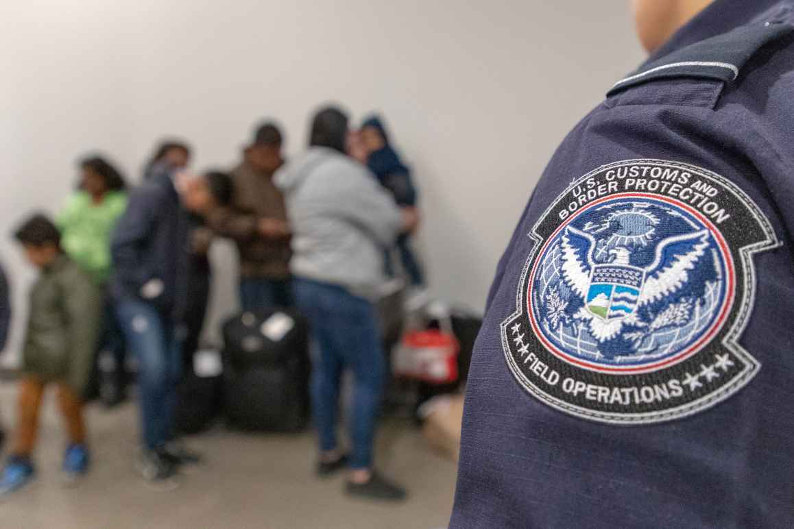 Badge on Customs and Border Patrol officer's uniform in focus with families lined up in background