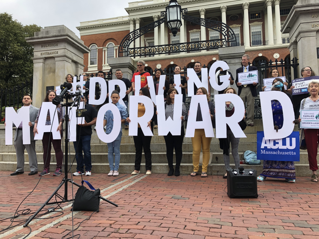 "Supporters hold letters spelling ""Driving MA Forward"" on State House steps"