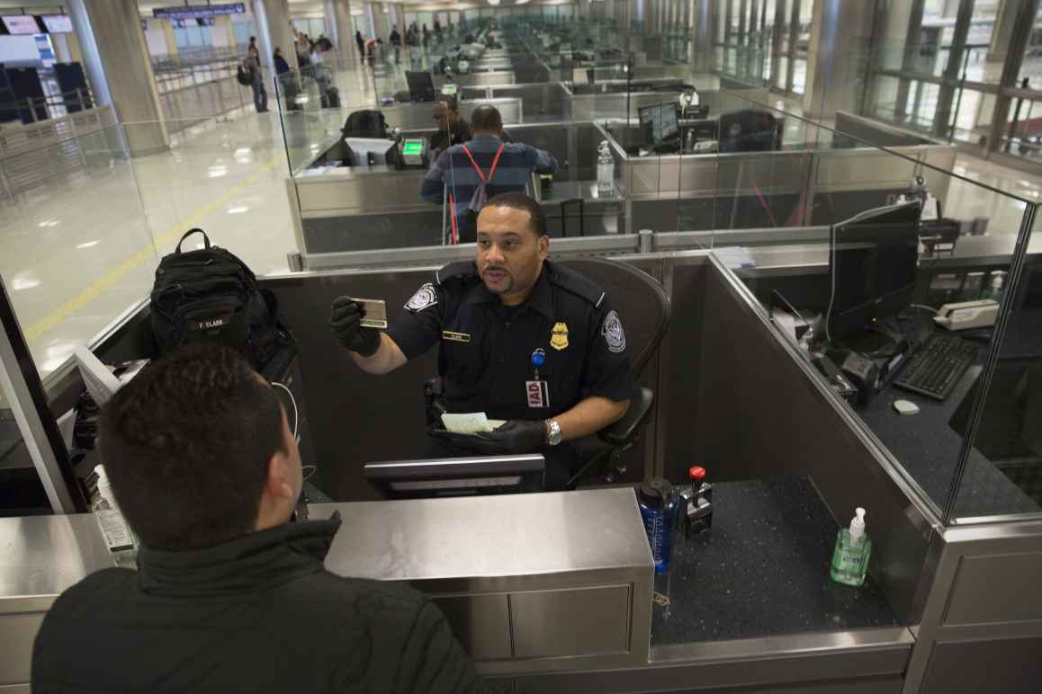 Customs and Border Patrol officer checks someone's passport at an airport
