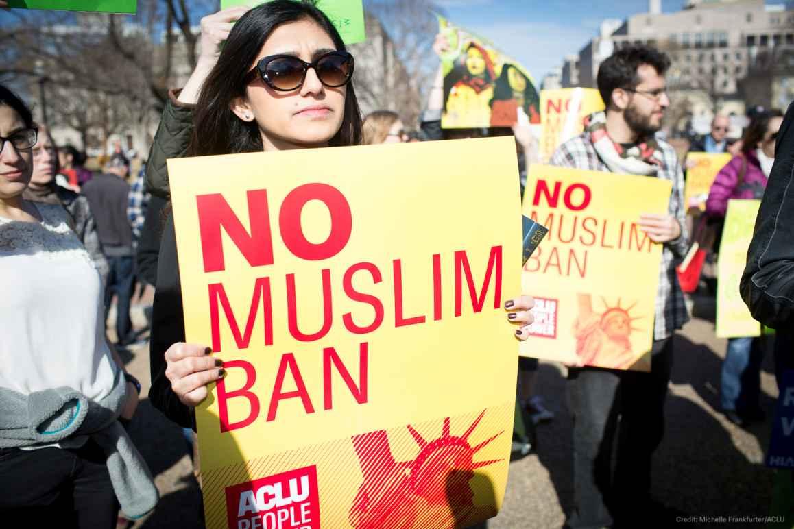 Woman holding No Muslim Ban sign
