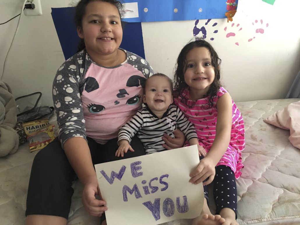 "Pereira Brito's three children sit on a bed with a handwritten ""We miss you"" sign"