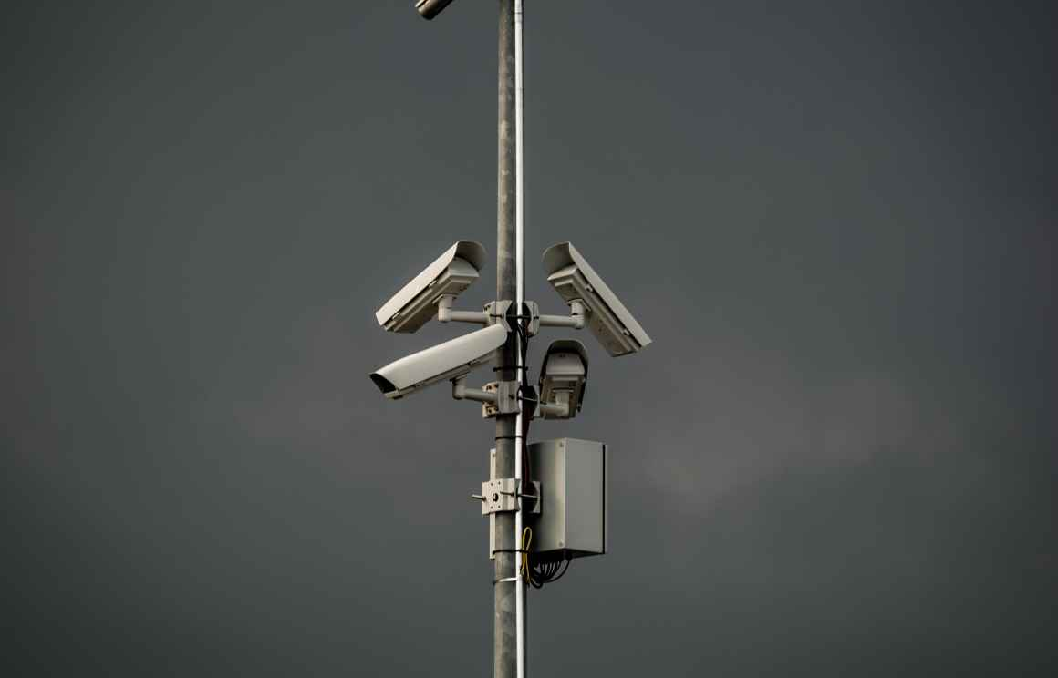 Three surveillance cameras mounted on a poll in front of gray sky