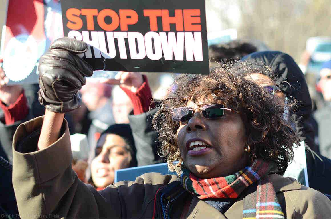 "Protestor stands with ""stop the shutdown"" sign"