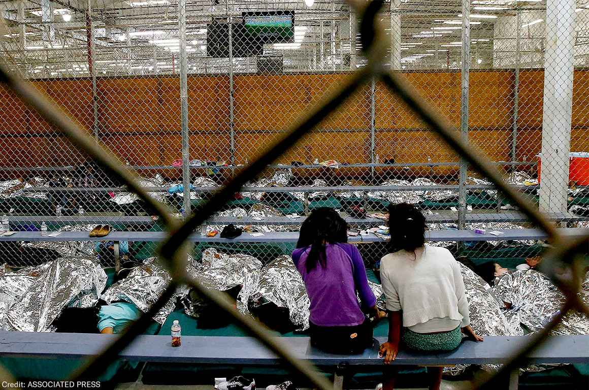 Two young girls watch a World Cup soccer match on a television from their holding area where hundreds of mostly Central American immigrant children are being processed and held