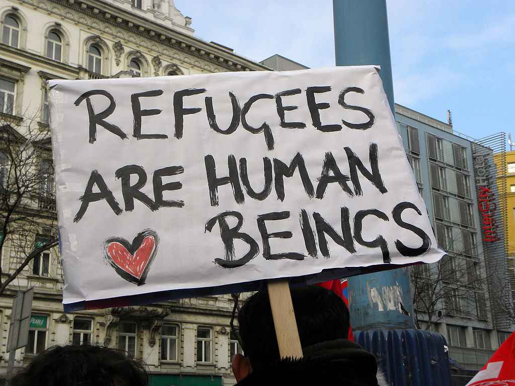 "Sign reads ""Refugees are human beings."""
