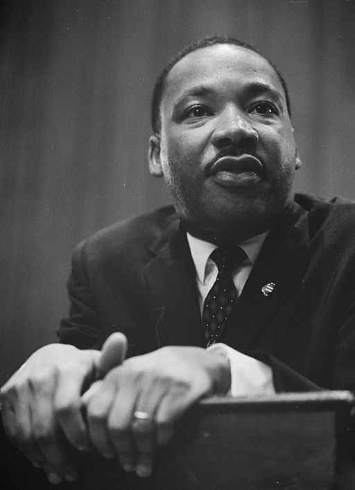 1964 photo of Martin Luther King Jr. leaning on a lectern