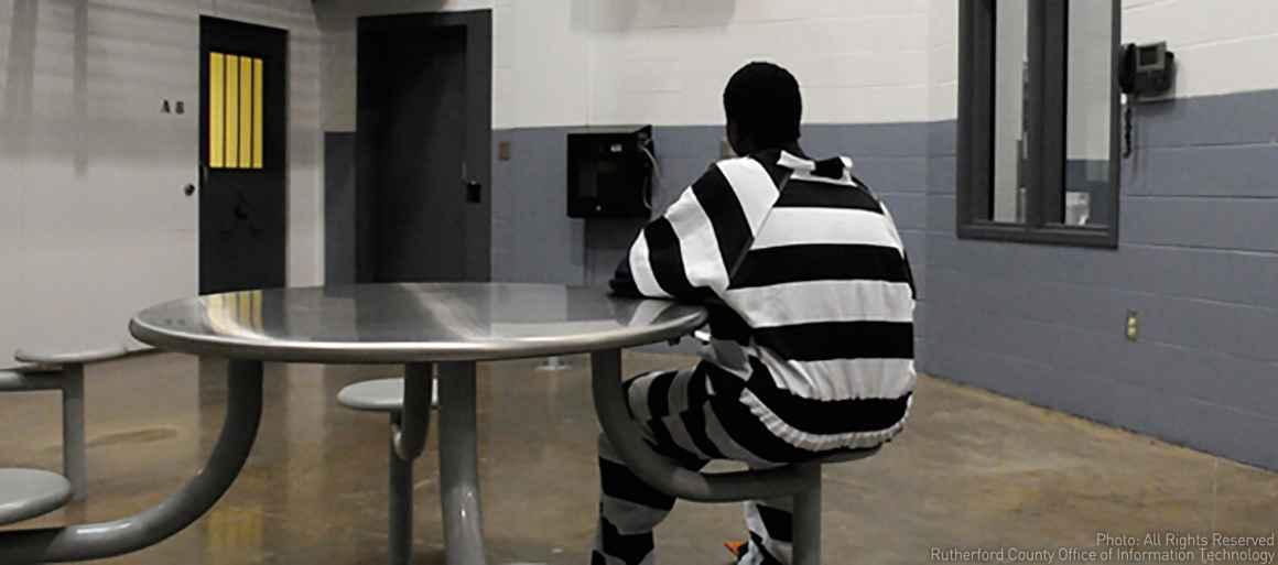 Incarcerated juvenile inmate sits at table