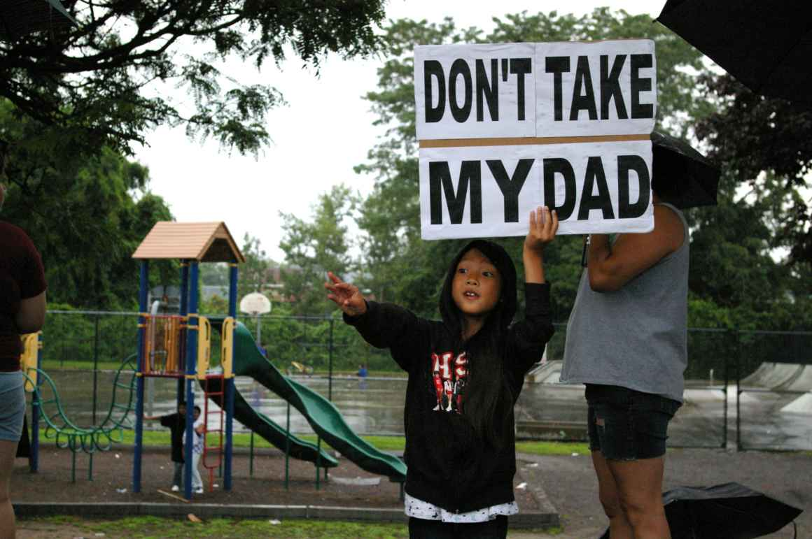 "A child holds a sign saying ""Don't take my Dad,"" after a raid on immigrants in Lowell, Mass."