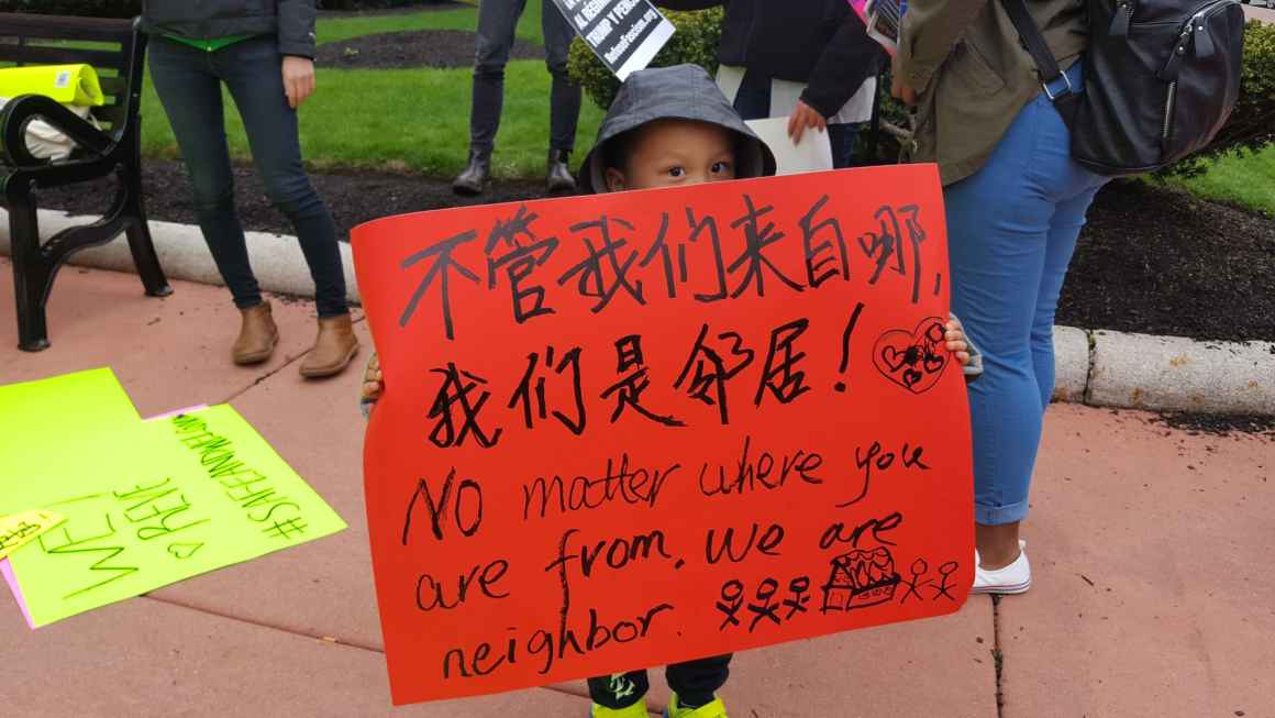 No matter where you are from you are our neighbor boy with protest sign