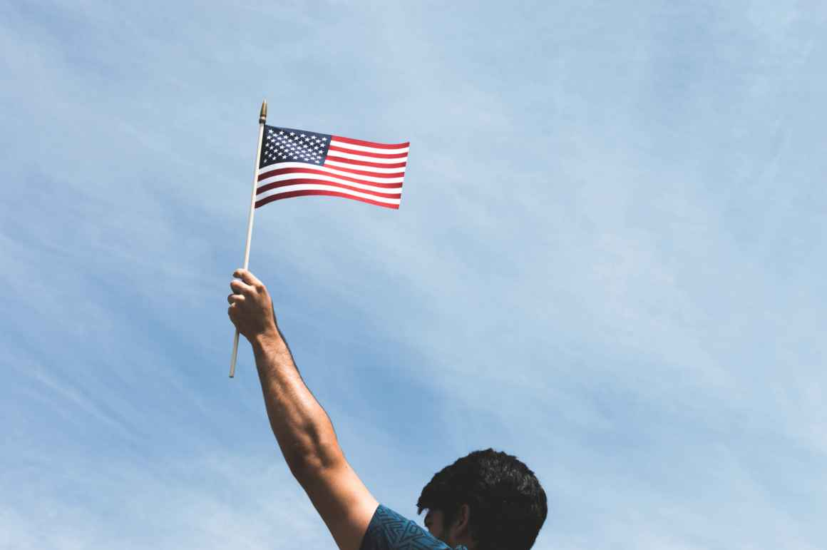 person holds american flag in front of blue sky